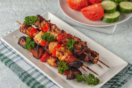 On a gray background barbecue of chicken on skewers with vegetables 版權商用圖片