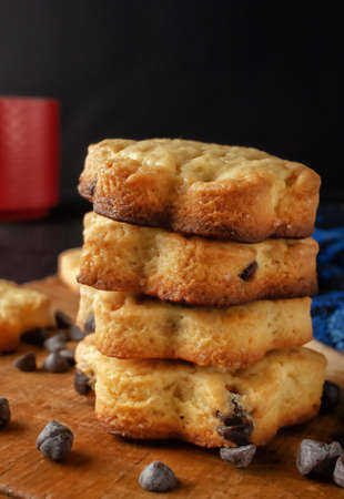 Fresh homemade cookies with chocolate on a wooden board on a dark background