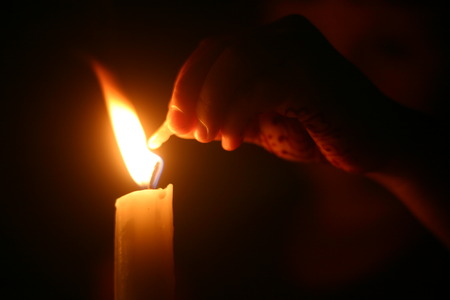 earthly: candle with hand Stock Photo