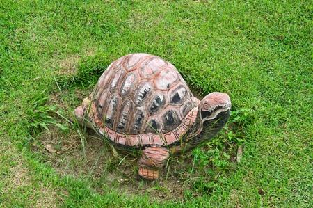impassive: Concrete turtle on the green grass.
