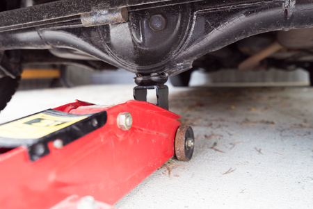 jacked: Car jack to lift car, changing car tire Stock Photo