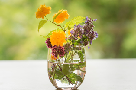 spring flowers in a glass vase on a table Imagens