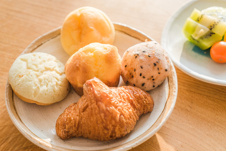 Bread and lots of fresh bread buns on a wooden table Stock Photo