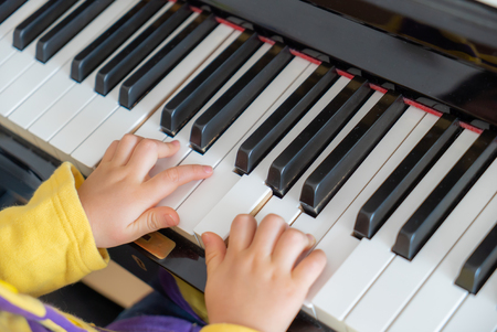 children's hands on the keys of the piano