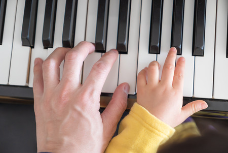 adult and a child's hand on a piano keyboard