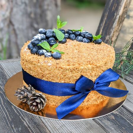 layer cake Napoleon with berries of blueberry on a rough wooden backgound sprinkled with powdered sugar