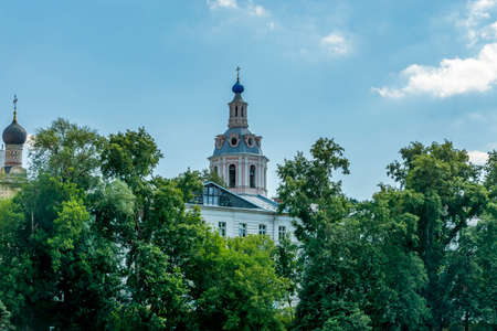 Russian Orthodox Church under blue sky and behind trees