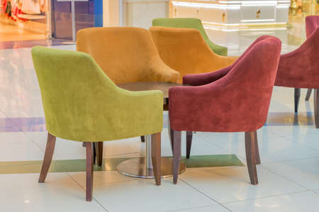 multicolored velvet armchairs around table in lounge zone