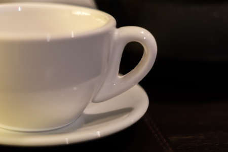 close up of white tea cup and saucer on table. Soft focus