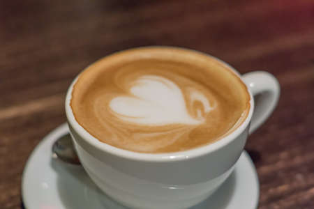 cup of cappuccino with heart on wooden table closeup Archivio Fotografico