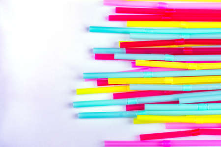 blue, pink and yellow straws for cocktails and other drinks isolated on white background