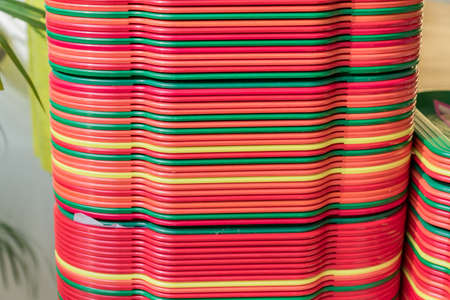 A stack of red, yellow, green trays on the table, close up.