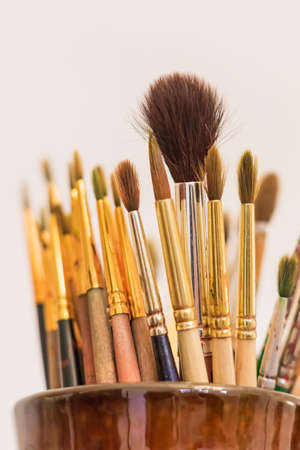 Brushes of the artist in clay pitcher on wooden shelf Standard-Bild