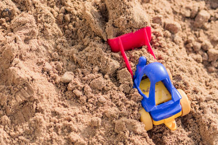 small toy digger working on sand quarry, construction concept