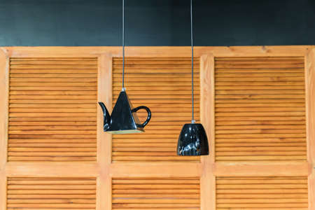 kitchen interior decoration. Lanterns in shape of kettle and cup on wooden panel wall background