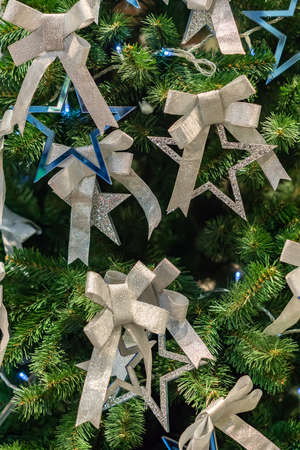 Christmas and New Year holidays background. Christmas tree decorated with silver bows and blue stars. Celebration concept