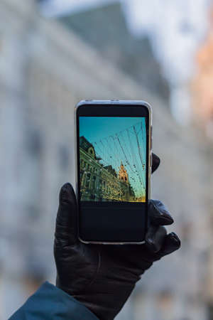 woman hand a black leather glove holding black smartphone for taking picture of christmas city in a sunny day