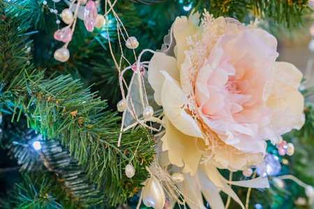 close up of christmas tree decorated with tender pink flower.