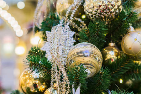 close up of christmas tree decorated with gold and white balls and snowflake. New year background