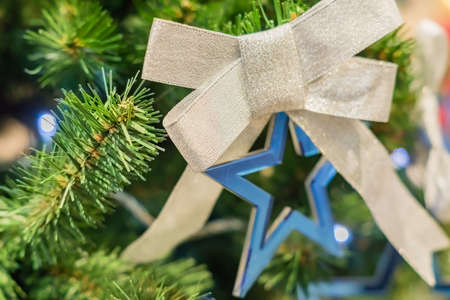 Christmas and New Year holidays background. Christmas tree decorated with silver bow and blue star. Celebration concept 免版税图像