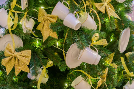 Christmas and New Year holidays background. Christmas tree decorated with white cups ans sauces. Trendy concept