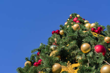 Christmas and New Year holidays background. Christmas tree decorated with balls and garlands against blue sky, bottom view