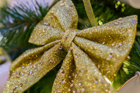 Christmas and New Year holidays background. Christmas tree decorated with gold sparkling bow. Celebration concept