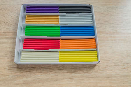 Set of multicolored plasticine bars for modeling on wooden table. Top view, eduction and creativity concept