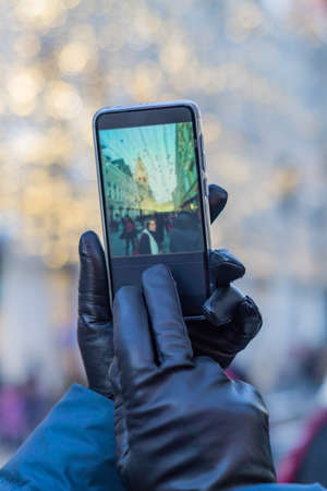 tourist taking picture of a woman in christmas city in a sunny winter day on smartphone camera. Bokeh background