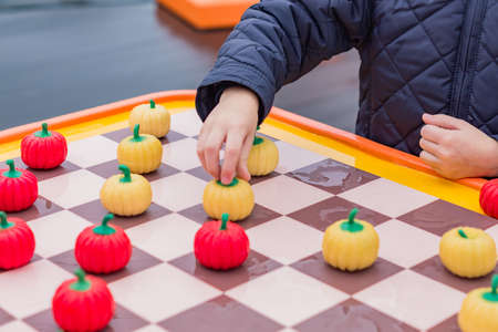 little boy in blue anorak playing pumpkin checkers with a man outdoors