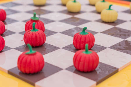 close up of checkered board with pumpkin checkers, colorful background