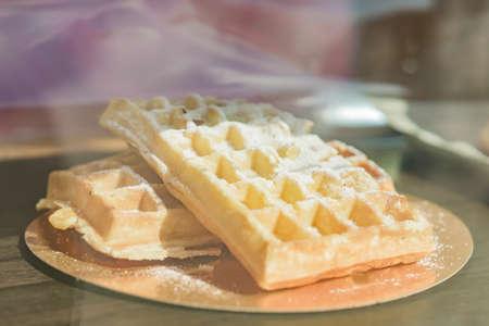 Freth baked Viennese waffles sprinkled with sugar powder on a caffe window shop