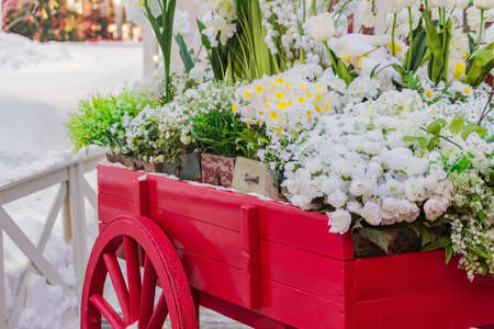 red wooden wheelbarrow with wooden boxes full of blooming artificial flowers. Street and garden decoration. Archivio Fotografico