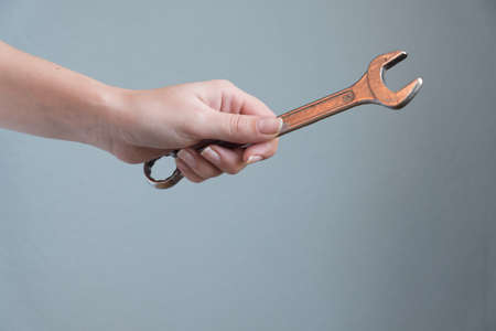 woman holding a wrench in her hand on gray background. Reklamní fotografie