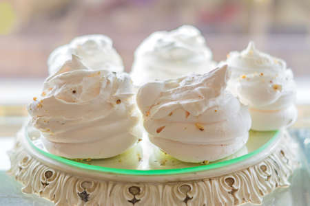 white air meringues on display plate at pastry shop