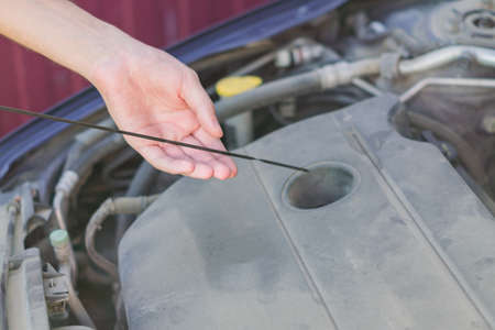 Mechanic checking and fixing an oil filler cap of a broken car on the road.