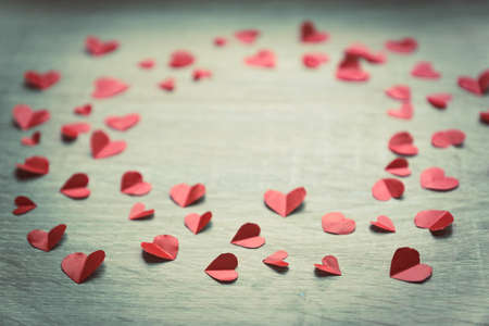 Plenty of cut out paper red hearts on wooden backround, perspective, toned, selective focus