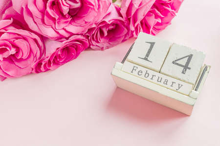 valentines day and holidays concept - close up of wooden calendar with 14th february date, and pink roses with on pink background