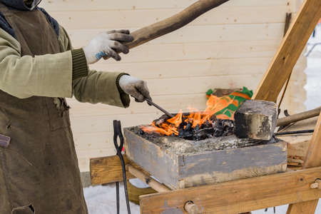 blacksmith manually forging the molten metal on the anvil outdoors Stockfoto