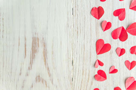 Plenty of cut out paper red hearts on wooden backround, selective focus. top view