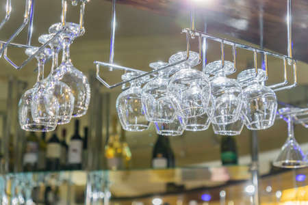 hanging glassware. Empty clean glass for vine and champagne at the bar. Selective focus