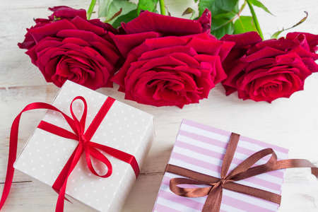 two gift boxes with ribbon bow and bautiful red roses on wooden background. Greeting card for holiday.