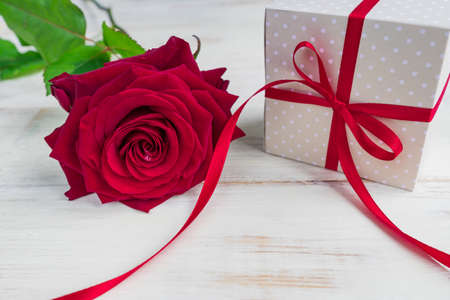 Beige polka dot gift box with red ribbon bow and bautiful red roses on wooden background. Greeting card for holiday. Foto de archivo