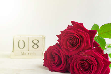 beautiful bouquet of red roses and wooden cube calendar on a wooden background. The concept of congratulations on March 8 or wooman's day.