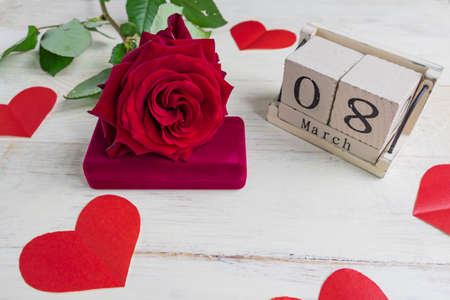 jewelry gift box with and bautiful red roses on wooden background. Greeting card for the 8th of March.