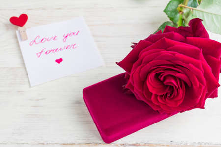 jewelry gift box and bautiful red rose on wooden background.