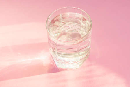 Close up of sparkling water in transparent glass and sun glare on pink background.