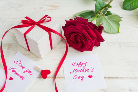 Beige polka dot gift box with red ribbon bow and bautiful red roses on wooden background. Greeting card for Mother's day