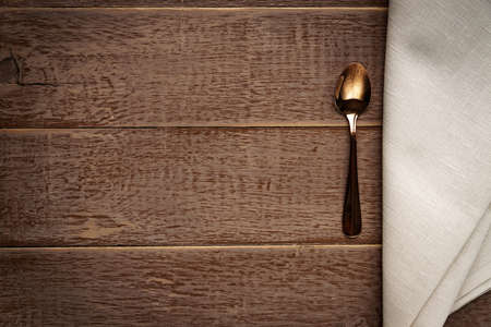 Top view of cloth napkin of beige color and served tea spoon on wooden table.