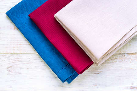 Top view of cloth napkins of beige, blue and burgundy colors on rustic white wooden background.